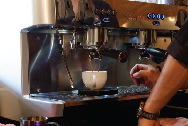 Um barista tirando um café espresso.