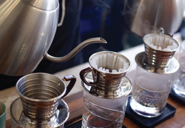 Um barista prepara café em duas Kalitas Wave ao mesmo tempo.