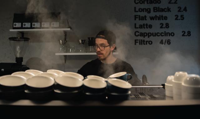 Um barista trabalhando atrás da máquina de espresso.