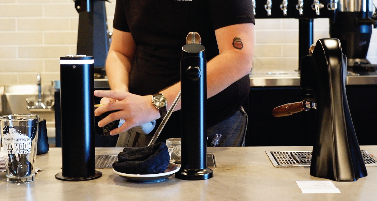A barista works with a modbar