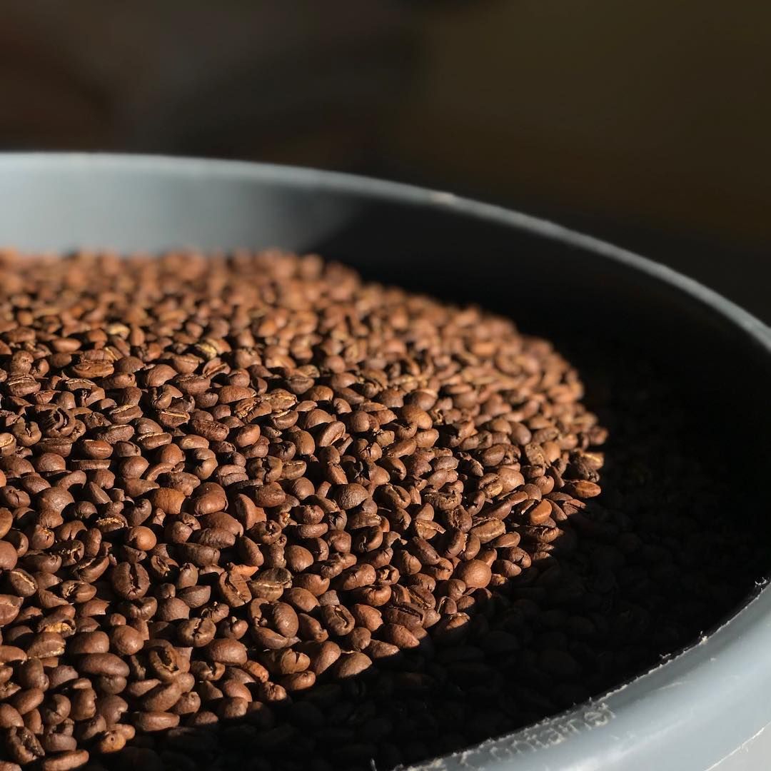 Black bowl with roasted coffee beans
