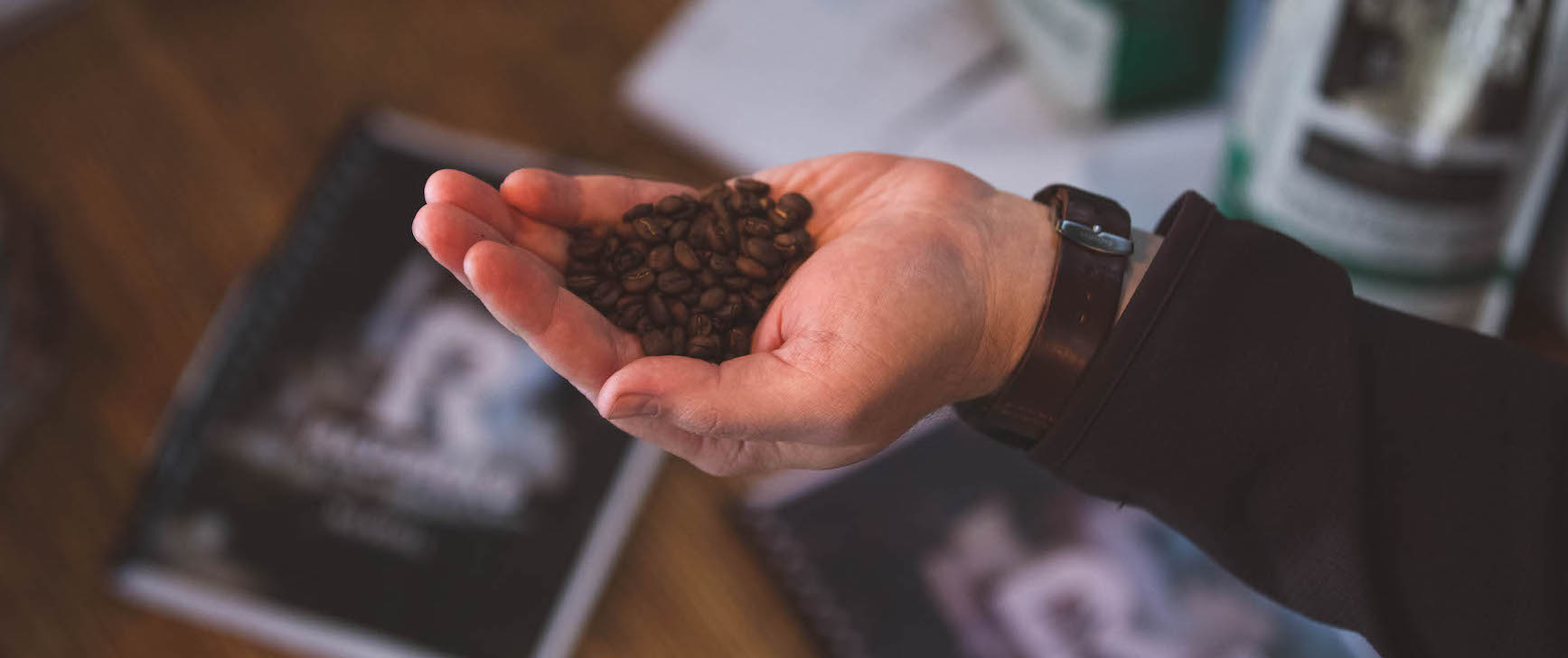 Hand holding roasted coffee beans