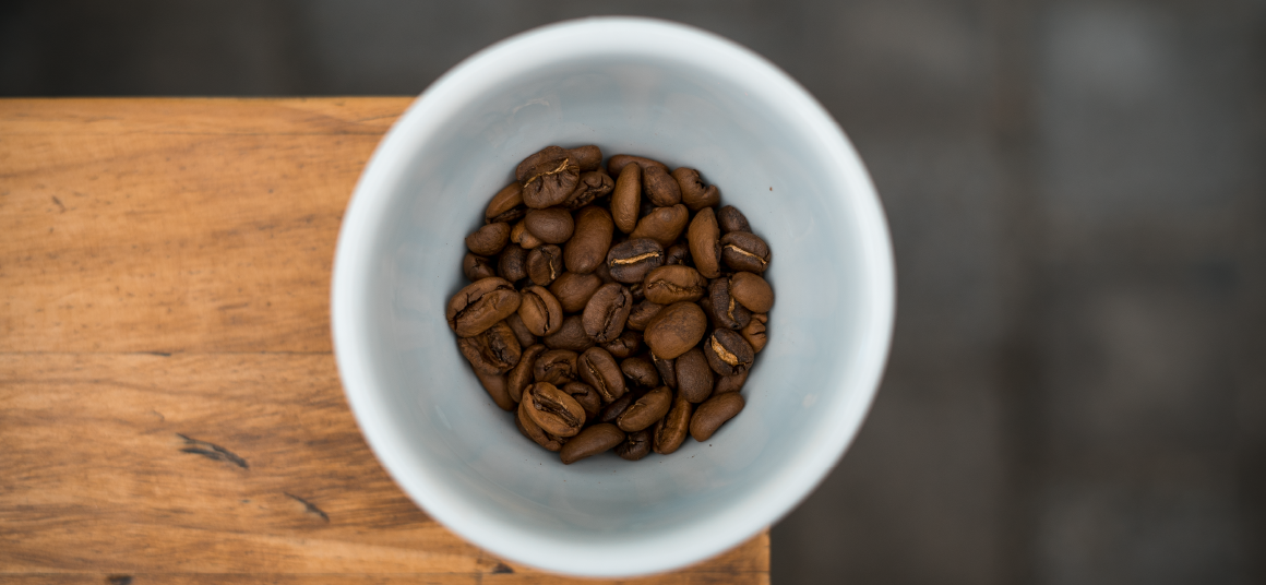 White mug with coffee beans in a wooden surface