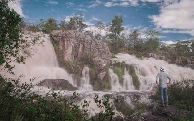 Marcelo Flanzer olha para uma cachoeira em sua fazenda de café em Minas Gerais, Brasil.