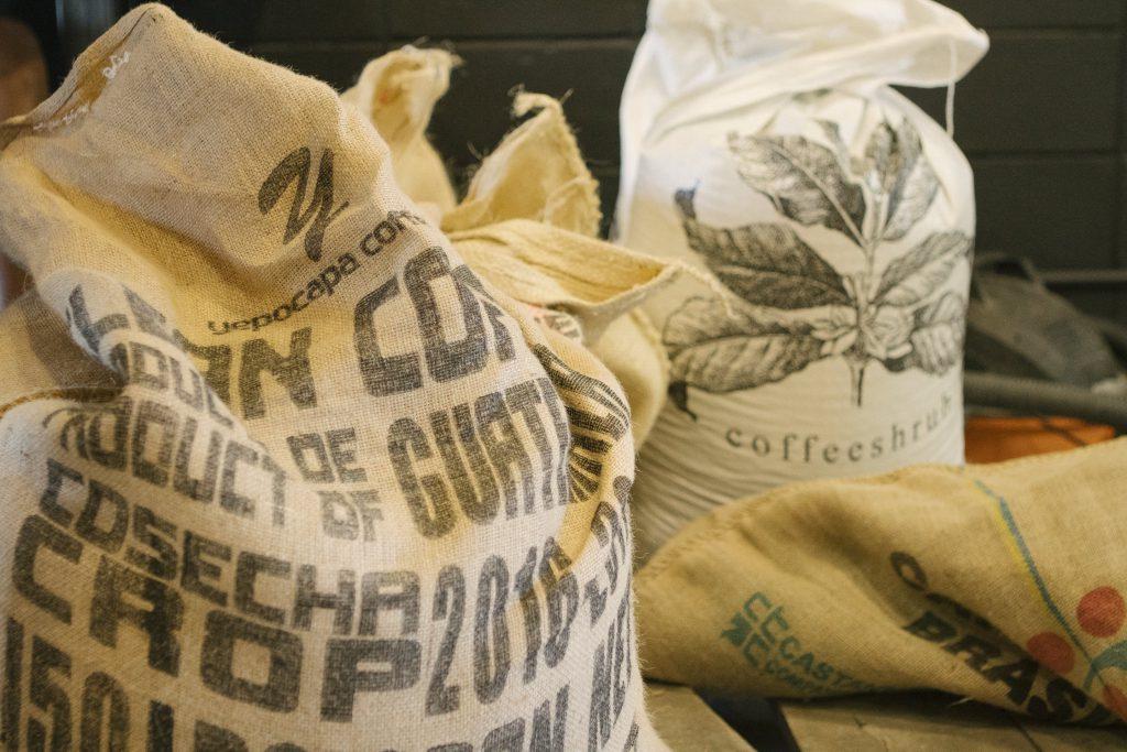 algunos sacos de cafe con granos verdes