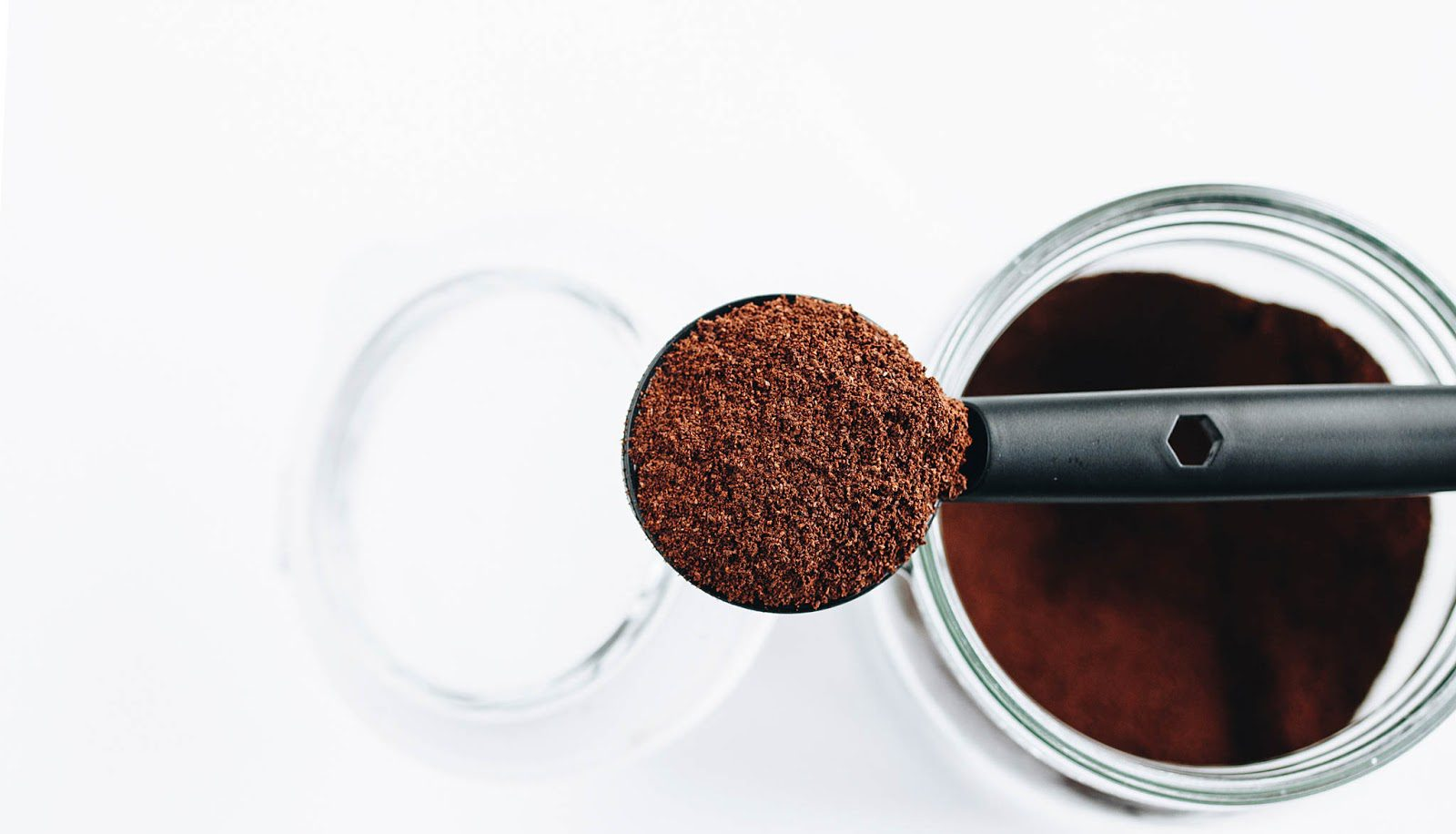 Black measuring spoon with grounded coffee above a glass jar