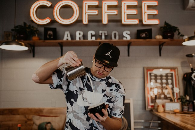 Barista pouring milk to make arte latte in a black cup