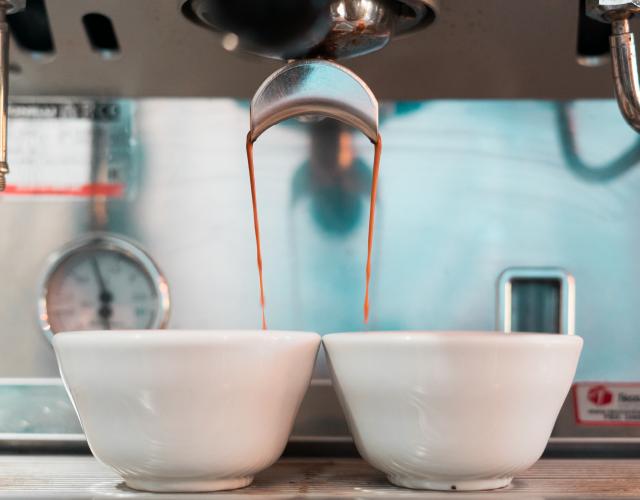 Espresso caindo em xícaras.