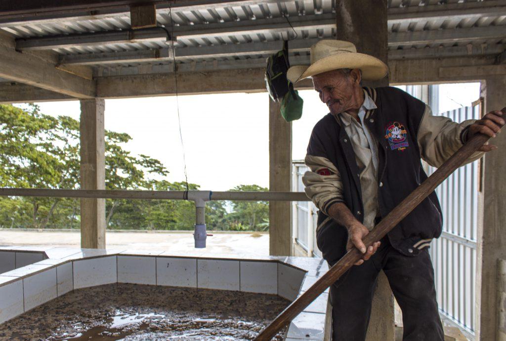 Um fazendeiro mexe no café em tanques de fermentação em uma fazenda em Honduras.