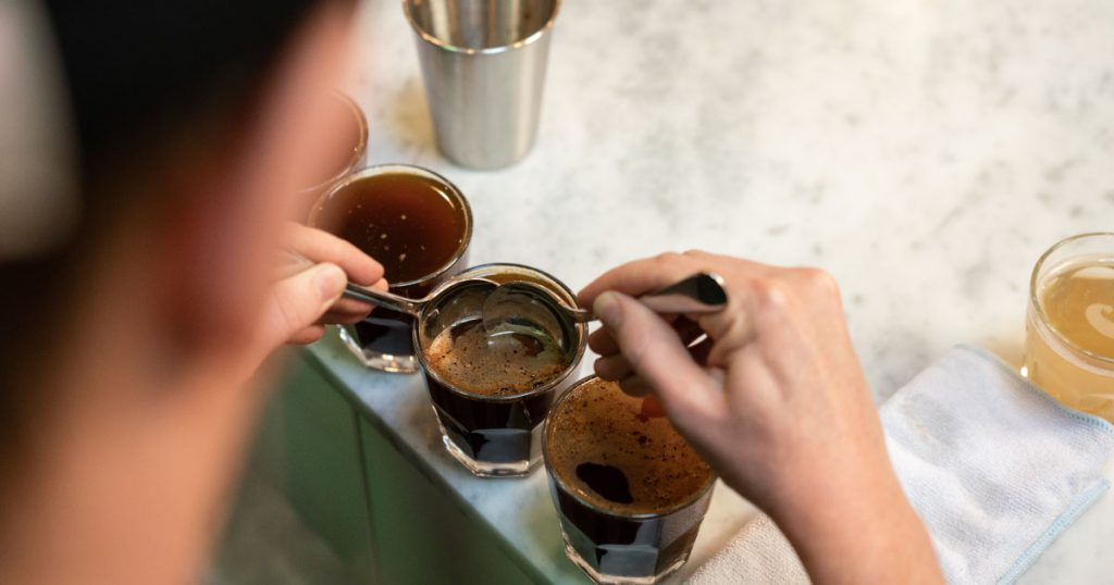 Barista breaking the crust during a cupping