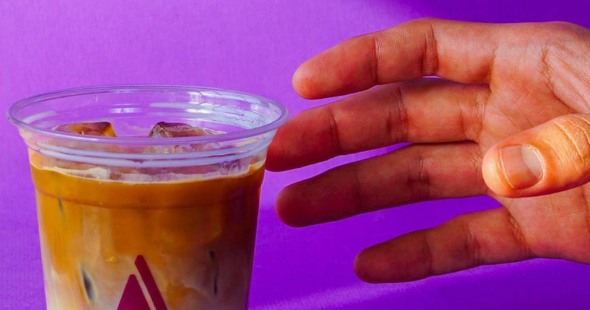Hand picking a glass with a iced latte. Purple background