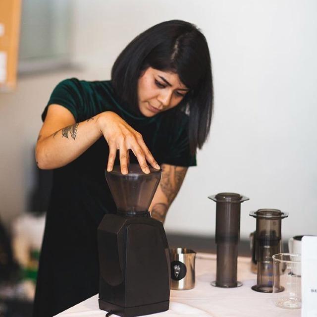 un barista muele su cafe en in molino de casa