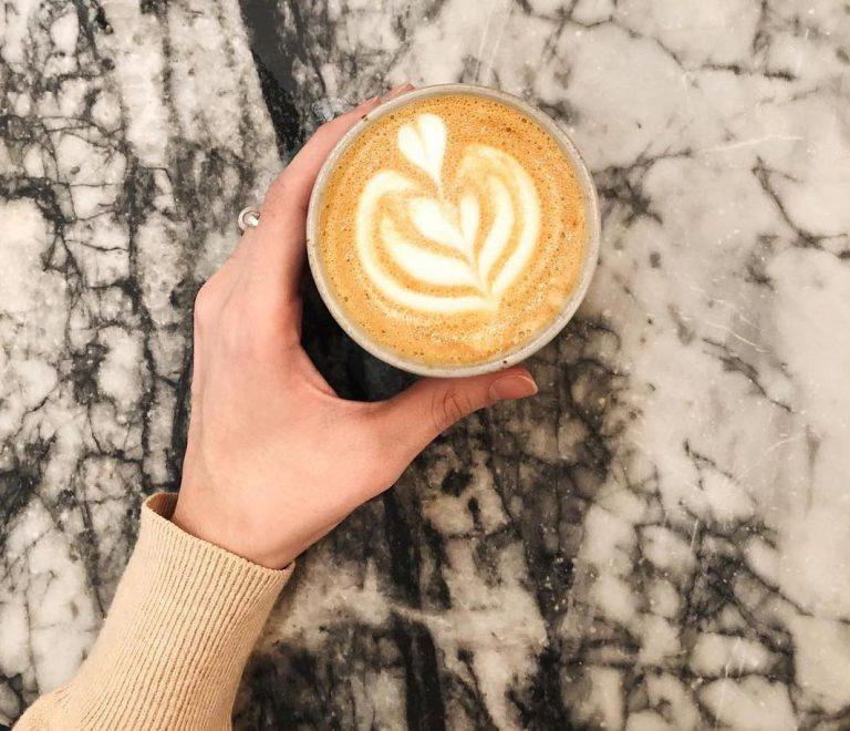 woman holding milk based coffee drink
