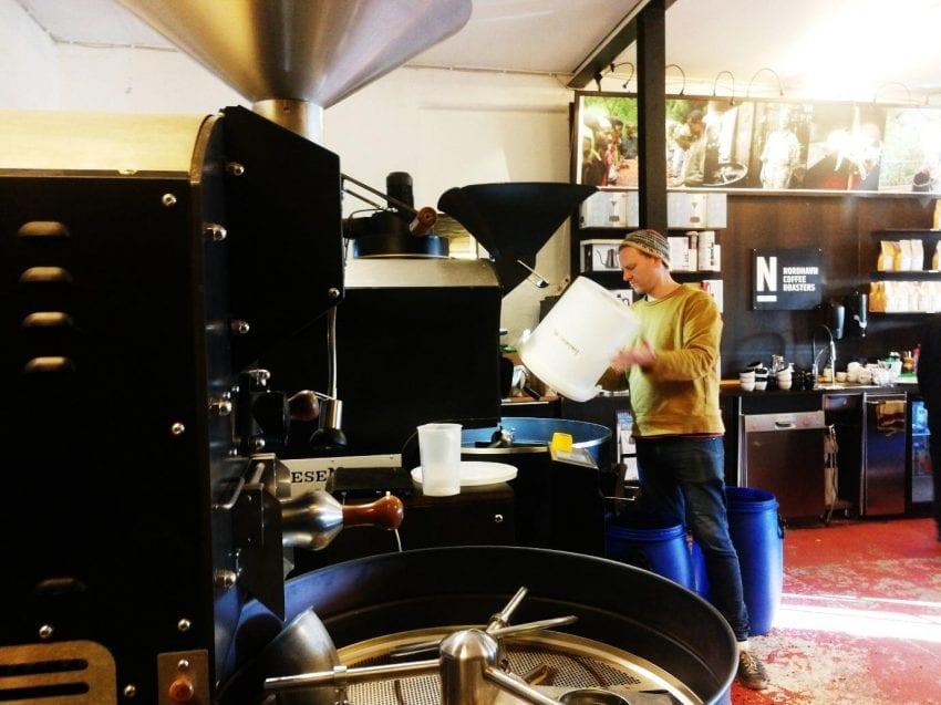 un tostador pone cafe verde a tostar