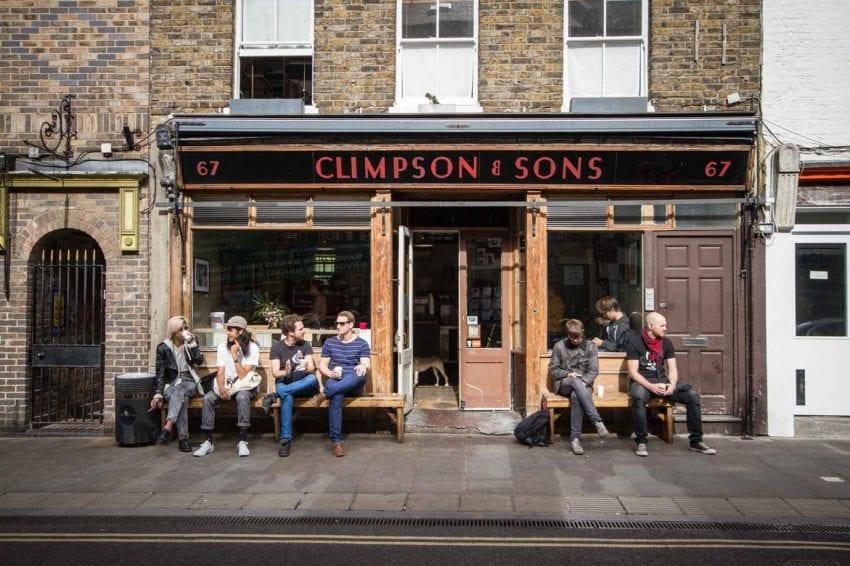 clientes sentados al frente de la tienda de cafe
