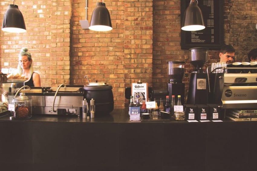 dos baristas preparando cafe para clientes