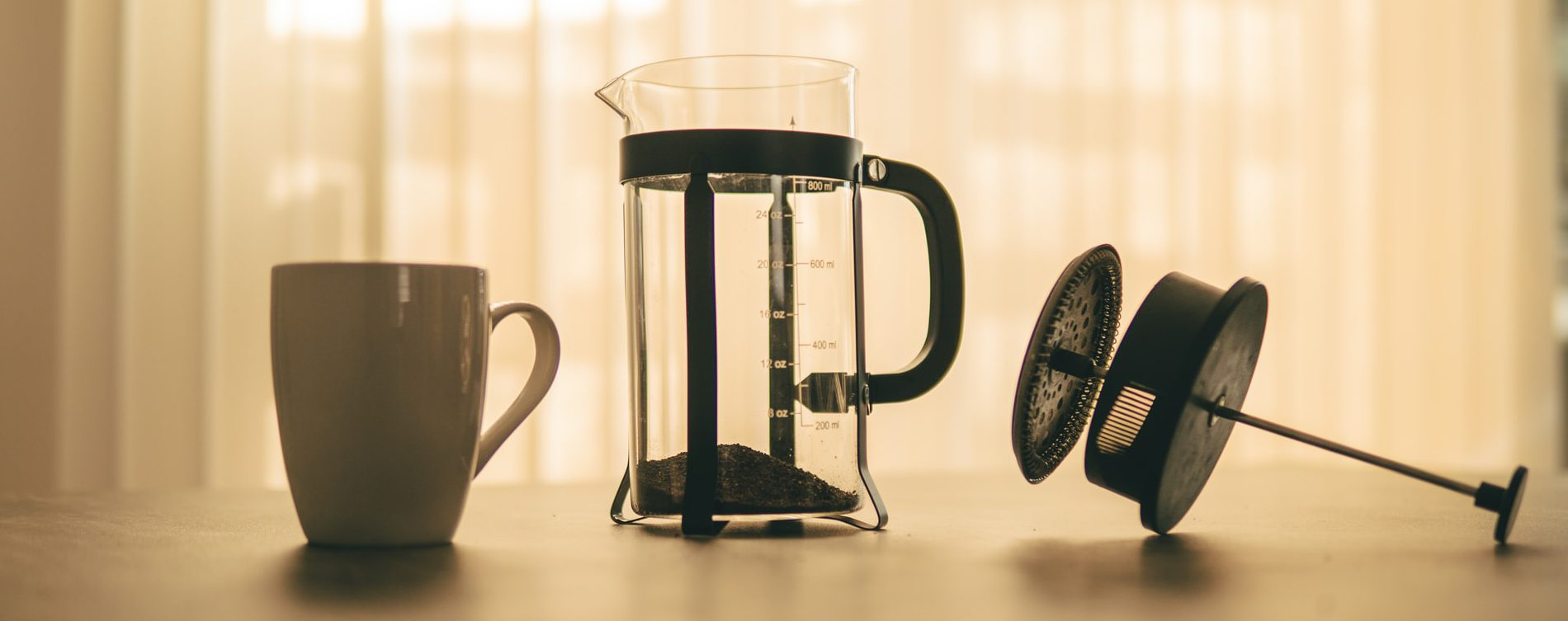 French press with ground coffee and a cup on a wooden surface