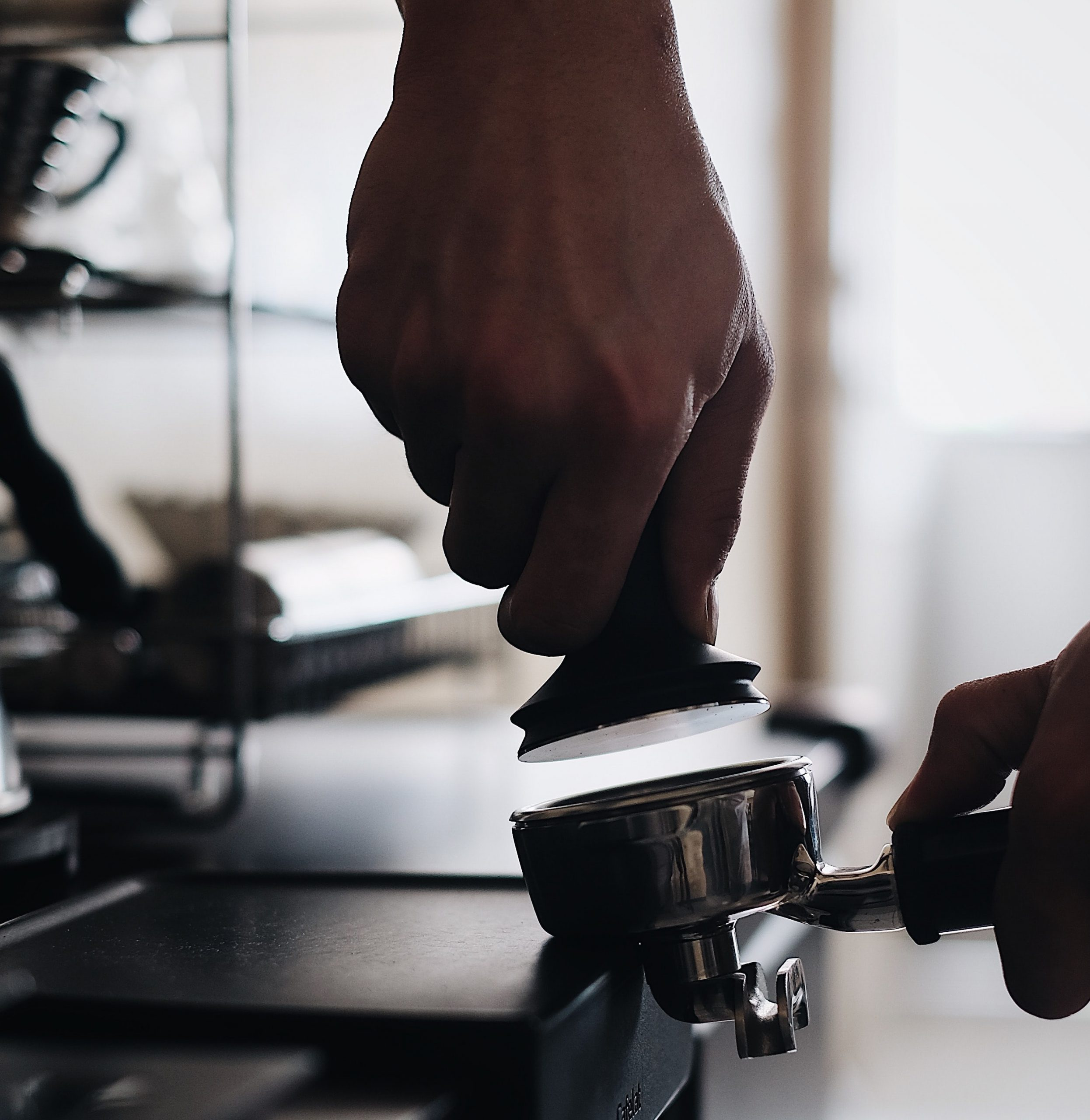 Barista tamping a coffee disc