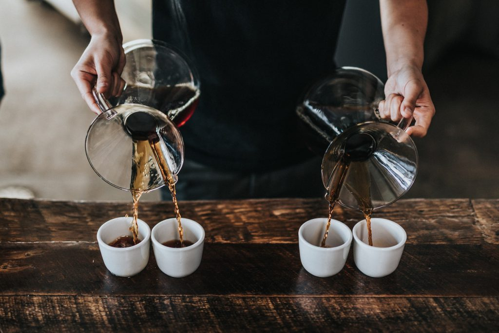 pouring four cups of coffee from chemex