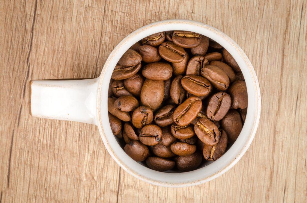 una taza de cafe llena de granos de cafe