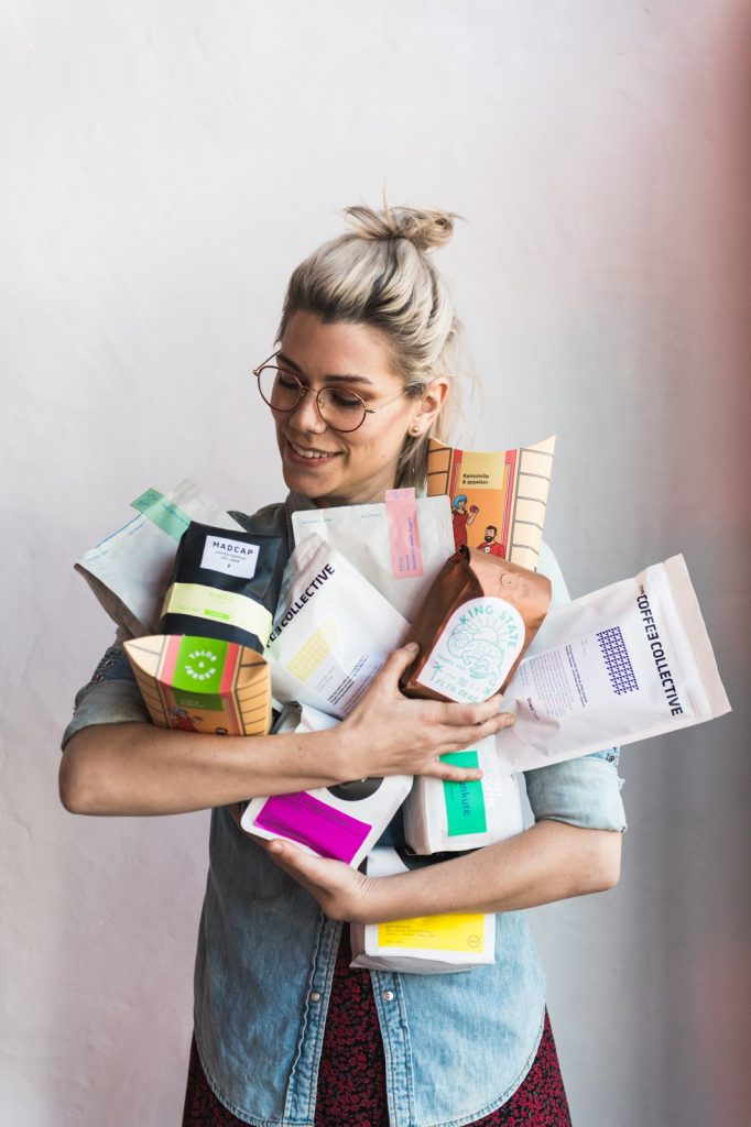 una barista sostiene varias bolsas de cafe