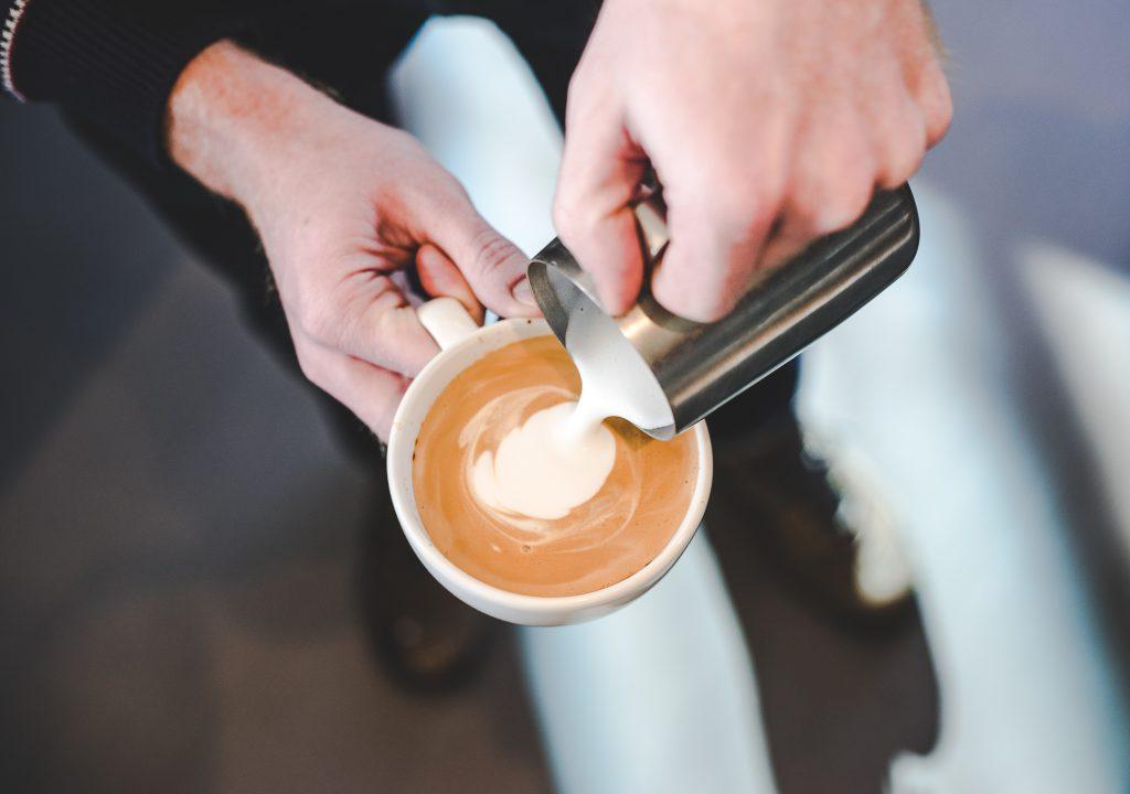 vertiendo leche a un espresso