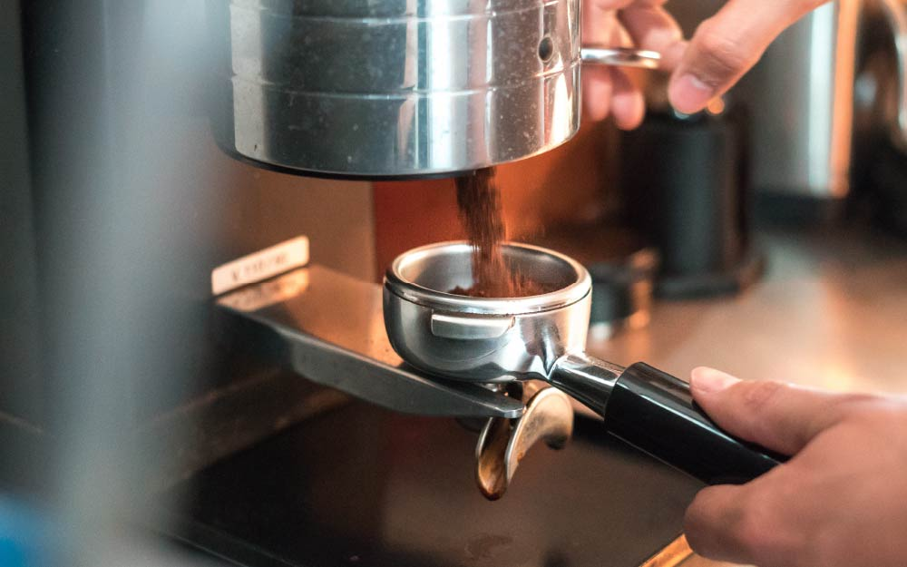 A barista grinding coffee for an espresso
