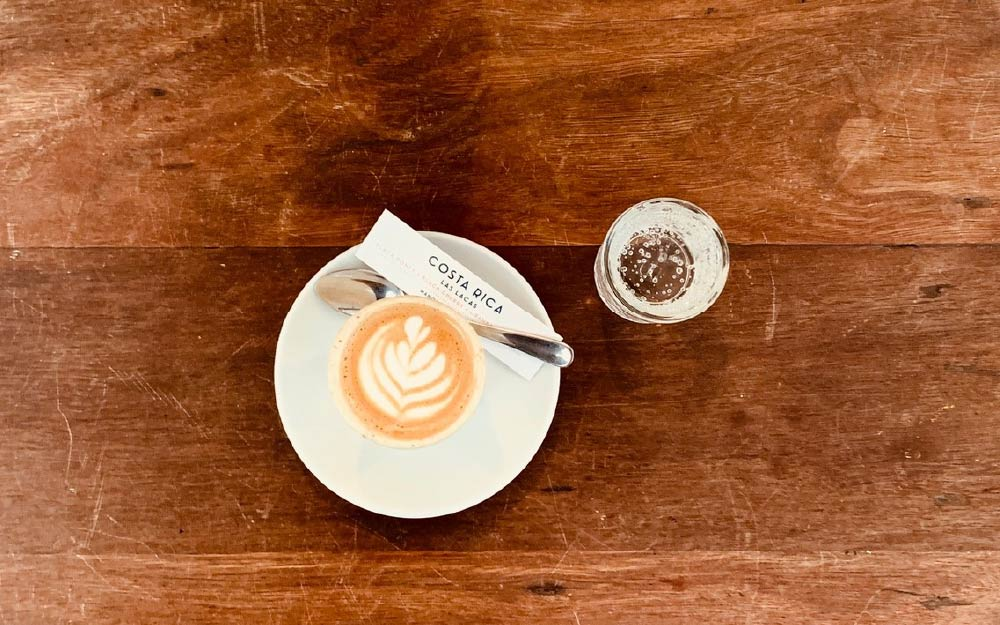Flat white in a white cup, with a glass of water in a wode surface seen from above
