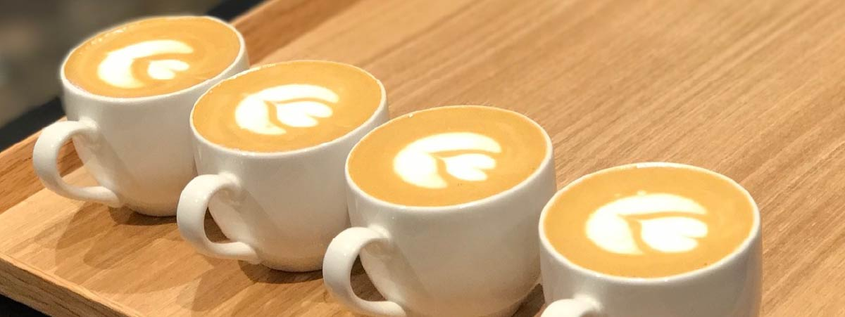 Line of flat white in white cups on a wooden surface