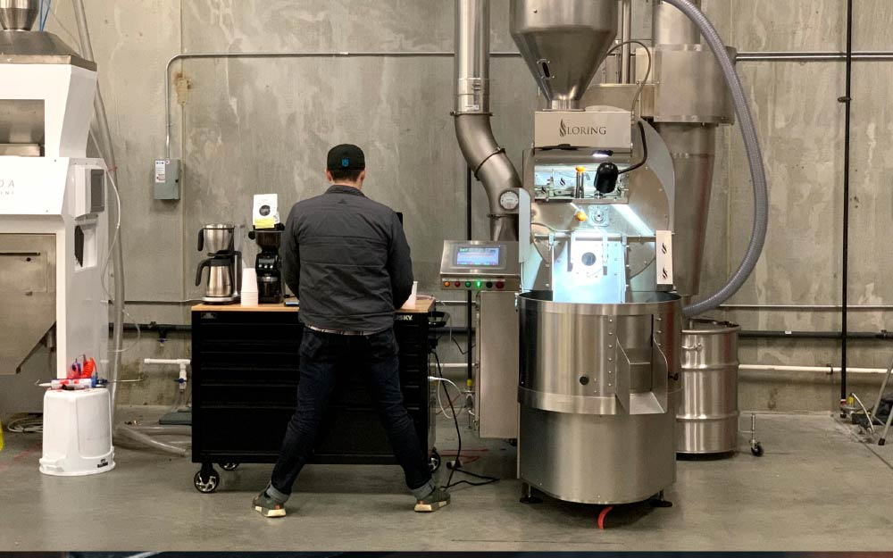 Roaster working at a roastery with a Loring machine