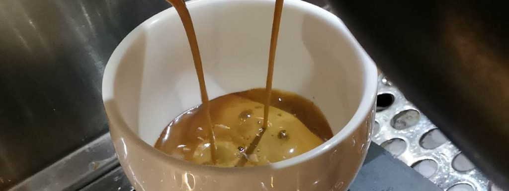Espresso falling into a white cup