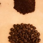 Samples of roasted coffee bean with respective grounded samples on an orange surface