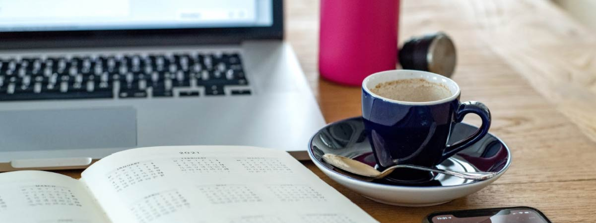 Blue espresso cup, an agenda and a computer on a wooden table