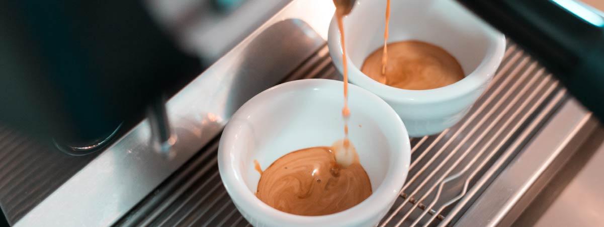 Espresso falling into two white cups