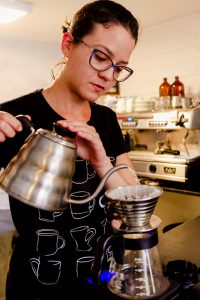 Woman brewing coffee with a kalita