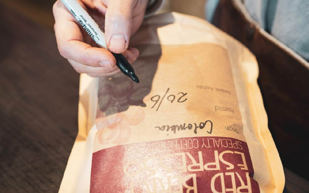 Roaster writing the date on the coffee bag, subscription