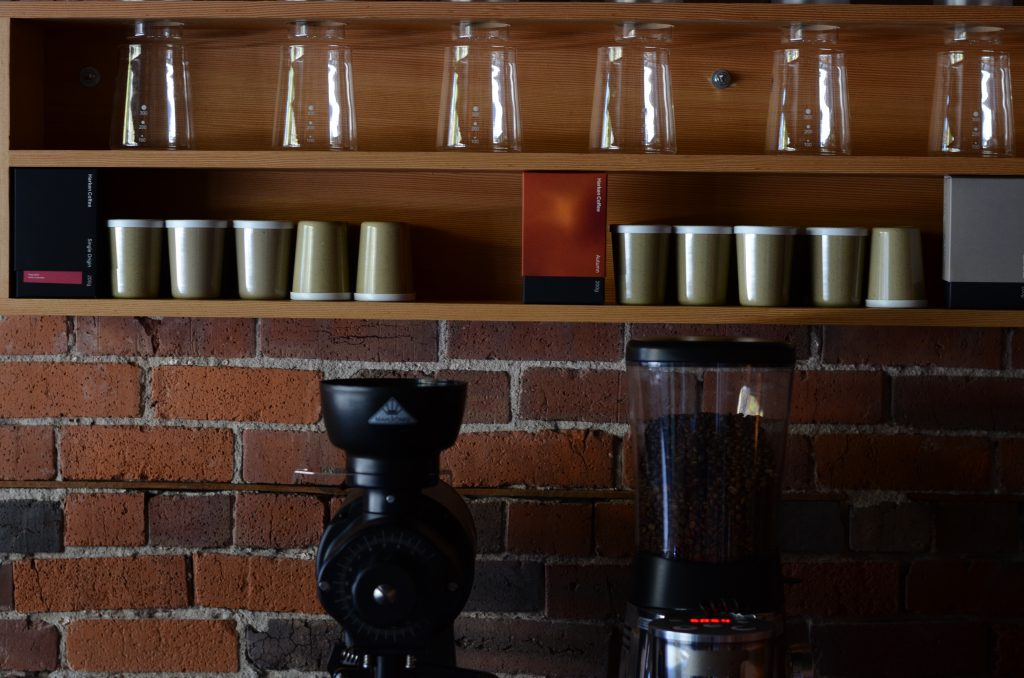 Café design, shelves with green coffee cups and glasses