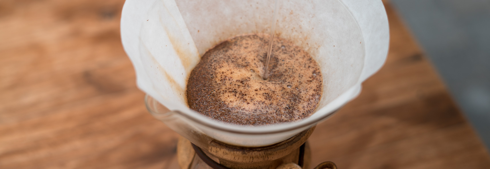 Barista brewing coffee into a chemex