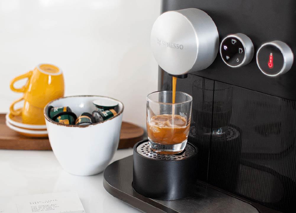 Espresso falling into a glass from a nespreso capsules machine, home coffee machine