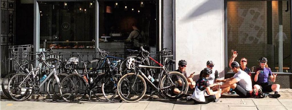 cyclist drinking coffee outside a local coffee shop