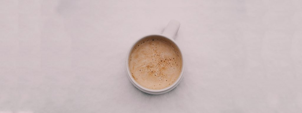 Flat white in a white cup on a marbeled surface