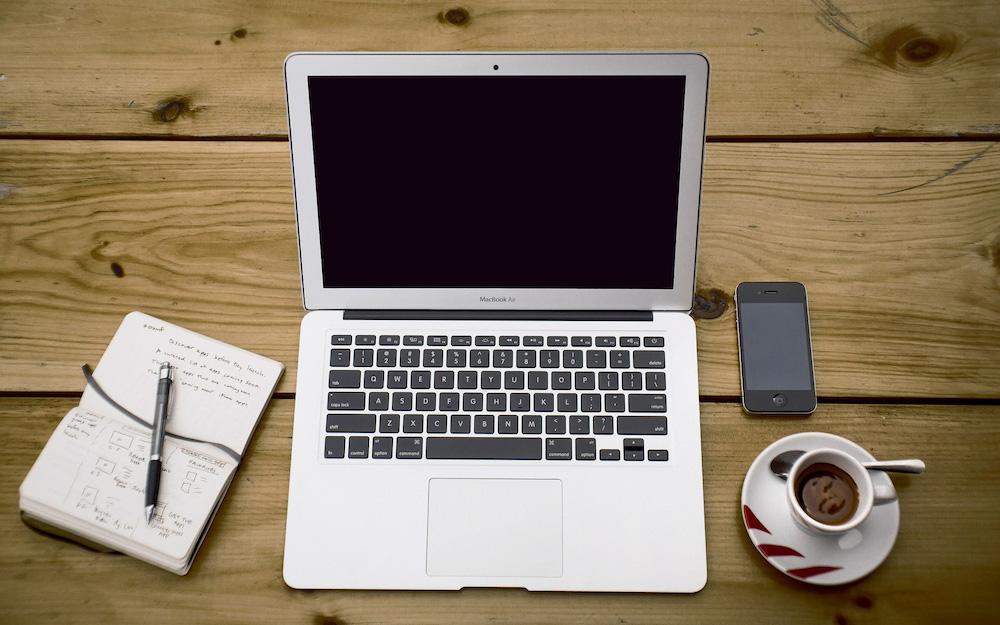macbook alongside notebook, iphone, cup of black coffee