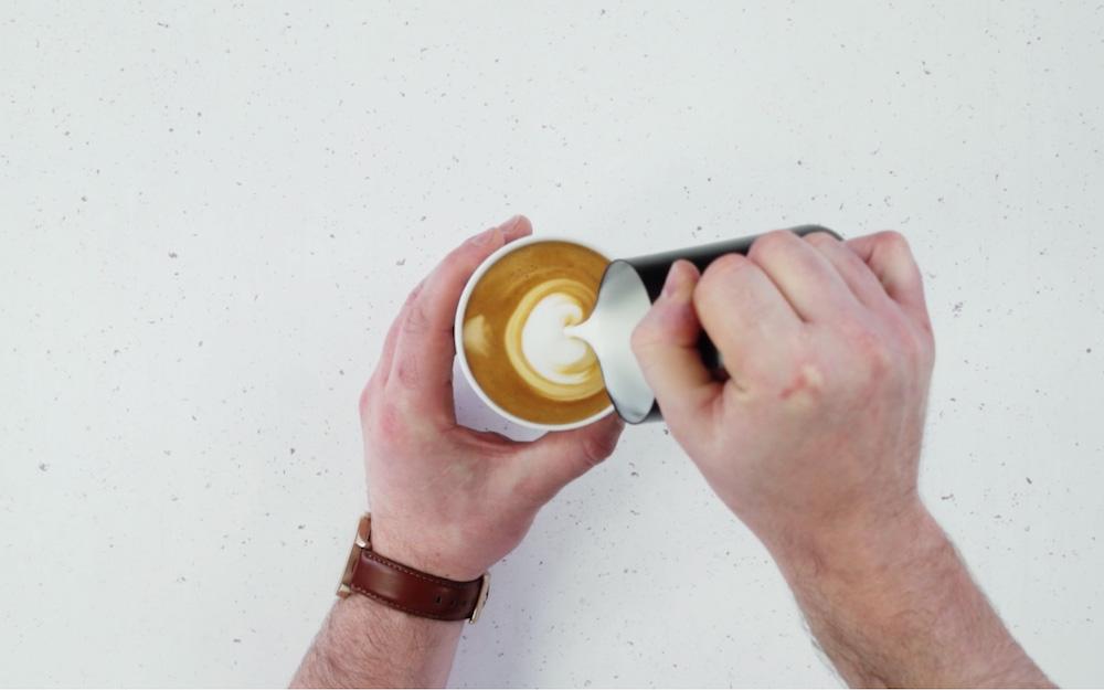 pouring steamed milk into espresso