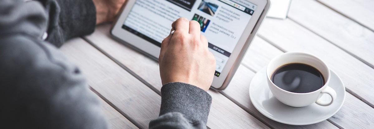 man working on tablet alongside black coffee